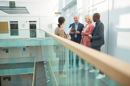 Businesswoman talking to her colleagues while they meeting at the corridor of office building