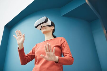 Young woman wearing virtual glasses playing in video games she standing and gesturing Stock Photo