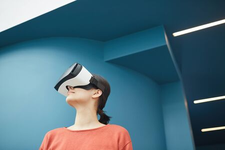 Young woman standing in virtual glasses she is in virtual reality