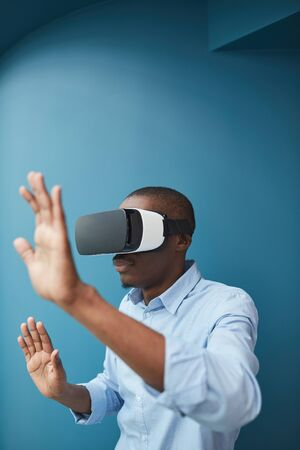 African man in virtual glasses gesturing he plaing in video game against the blue background