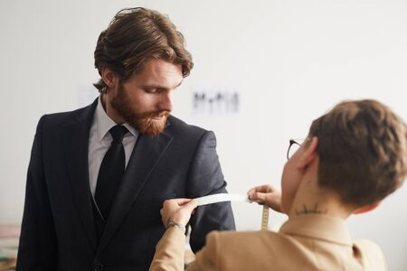 Bearded young man wearing suit while tailor taking measurements with tape measure in the workshop Banco de Imagens