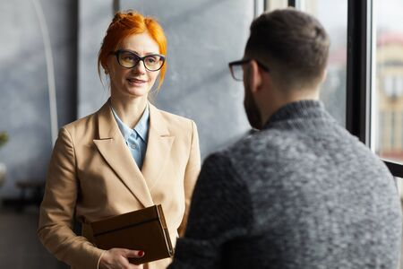 Red haired businesswoman in eyeglasses talking to businessman while they standing at office corridor