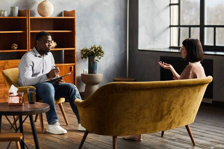 African psychologist sitting on chair and talking to young woman they discussing some problems during psychology therapy