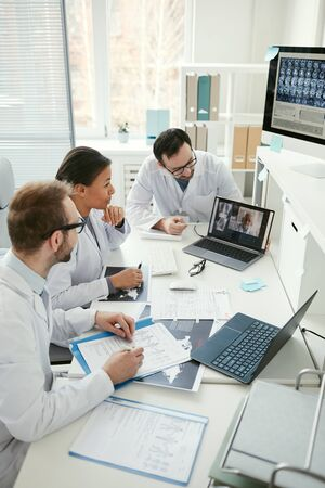 Group of doctors sitting at the table and talking to their colleague during online conference at meeting
