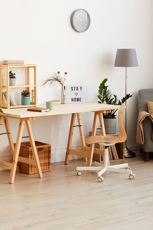 Image of modern wooden table with flowers and notepad in the room at home