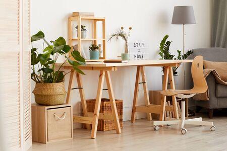 Bild eines modernen Holztischs mit Blumen und Sofa in der Nähe im Wohnzimmer zu Hause