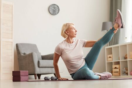 Mature woman sitting on the floor and stretching her leg during sports training in the living room at home Imagens
