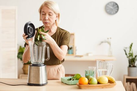 Mature woman making healthy cocktail from spinach and fruits using blender while standing in the kitchen Stock Photo