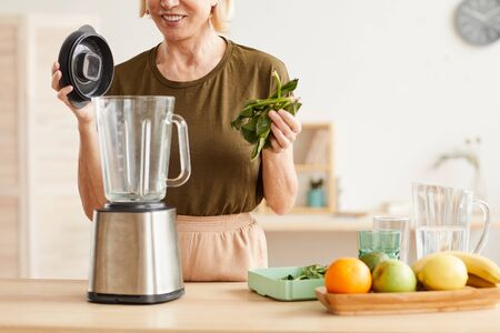 Close-up of mature woman putting spinach into the blender she is going to make a healthy cocktail Stock Photo