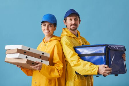 Portrait of young couple in uniform delivering pizza they standing against the blue background and smiling at camera