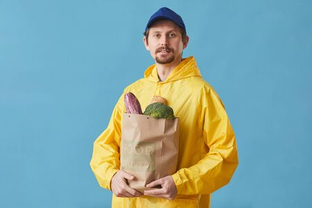 Portrait of young man in uniform holding paper bag with products against the blue background he delivering food Reklamní fotografie