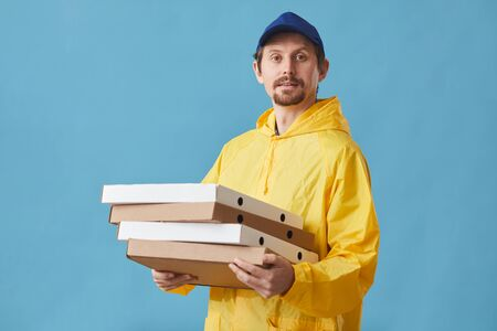 Portrait of young man in uniform holding pizza boxes and looking at camera against the blue background he delivering pizza