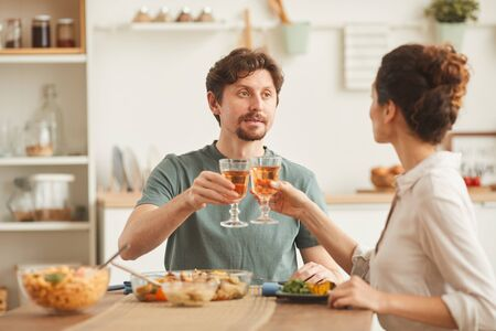 Young couple sitting at the table drinking wine and eating dinner in the domestic kitchen
