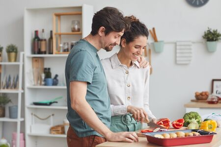 Young couple preparing food together in the kitchen they preparing dish from vegetables