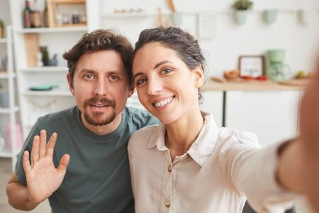 Portrait of young couple smiling at camera they making selfie at home Standard-Bild