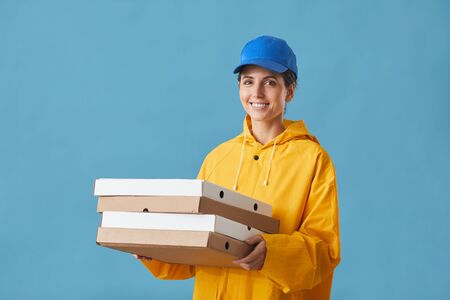 Portrait of young woman in uniform holding pizza and smiling at camera against the blue background