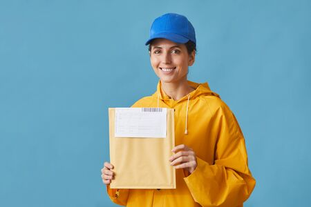 Portrait of young postwoman in uniform holding letter and smiling at camera against the blue background