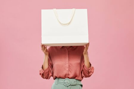 Young woman hiding before the big white shopping bag while standing against the pink background