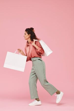 Young woman with curly hair walking with big paper bags against the pink background 免版税图像