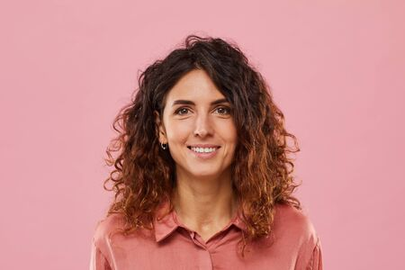 Portrait of young woman with curly hair smiling at camera isolated on pink background