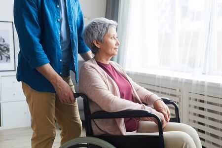 Disabled senior woman sitting in wheelchair and looking through the window with caregiver standing nearby
