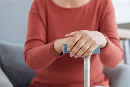 Close-up of senior woman sitting on sofa and holding crutch