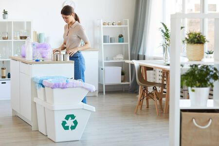 Young woman standing at the kitchen table and recycling plastic bottles and can Stock Photo