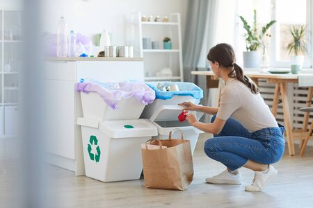 Young woman sorting plastic and paper into the different bins in the kitchen at home