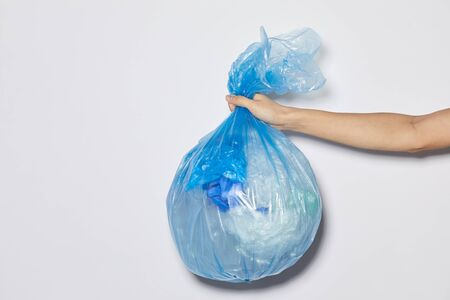 Close-up of female hand holding package with garbage against the white background
