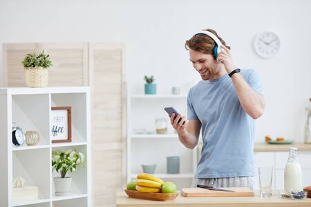Young man wearing headphones smiling while standing in the kitchen and talking on mobile phone