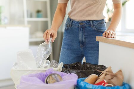 Close-up of woman holding plastic bottle and throwing it into the trash bin