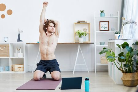 Young muscular man sitting on exercise mat and raising his hands up in the living room at home