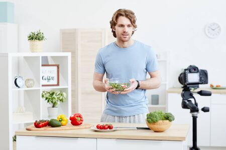 Young man holding bowl with salad and telling how to cook vegetable salad online on camera in the kitchen