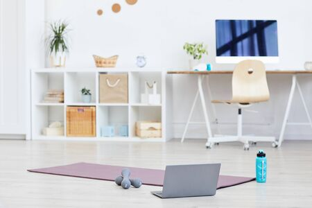 Exercise mat with dumbbells and laptop on the floor prepared for sports training at home