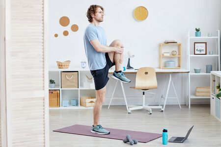 Young man standing on exercise mat and doing sports exercises in the room at home
