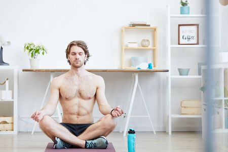 Young shirtless man sitting on the floor in lotus position and meditating with his eyes closed at home
