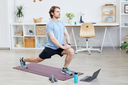 Young man exercising on exercise mat he watching online sports training on laptop at home