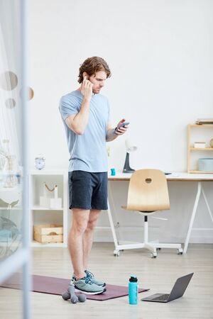 Young man standing on exercise mat and using his mobile phone during sports training at home