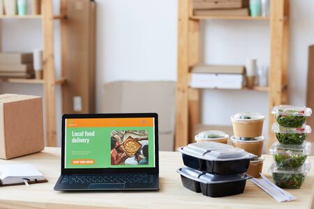Image of laptop with website of food delivery service and boxes of food on the table at office