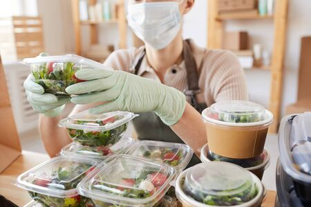 Close-up of young woman in protective mask and gloves packing fresh vegetables in boxes while sitting at the table Foto de archivo