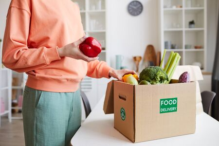 Close-up of young woman unpacking the fresh vegetables from the box while standing in domestic kitchen