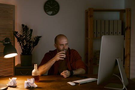 Mature man sitting at his workplace in front of computer monitor and drinking alcohol after work at office