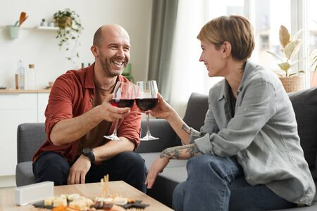 Mature man smiling to woman while they sitting on the sofa and drinking wine from wineglasses