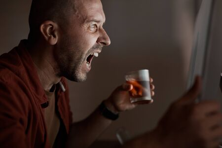 Matue man sitting in front of computer monitor and shouting he drinking alcohol and he has a problem with work Imagens