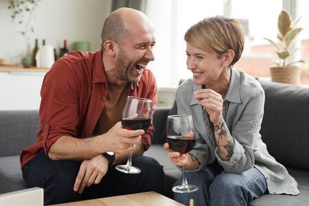 Happy couple sitting on the sofa with wineglasses of wine and laughing they spending funny time together