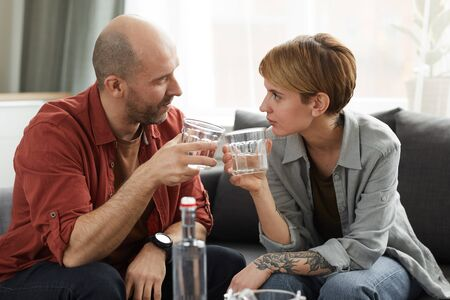 Young couple with glasses of scotch talking to each other while sitting on sofa in the living room at home Zdjęcie Seryjne