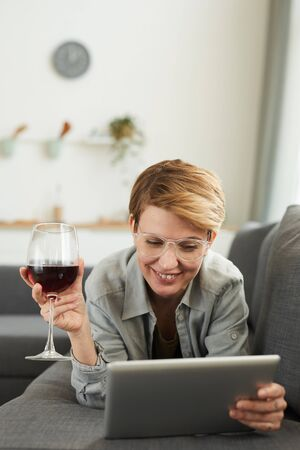Young woman in eyeglasses lying on the sofa using digital tablet and drinking red wine from the wineglass