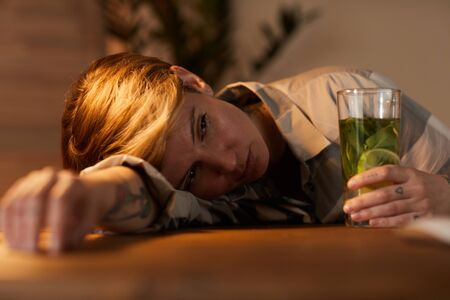 Young drunk woman lying on the table she drinking alcohol cocktail