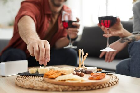 Close-up of wooden tray with different kinds of cheese on the table with couple drinking wine in the background