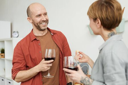 Mature man smiling and talking to the woman while they tasting red wine with cheese